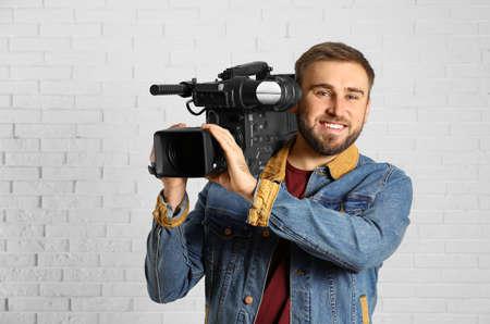 Operador con cámara de video profesional cerca de la pared de ladrillo blanco.
