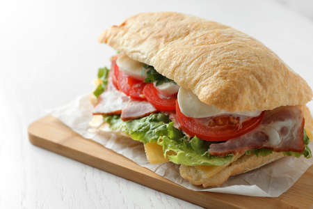 Delicious sandwich with fresh vegetables and mozzarella on white table, closeup