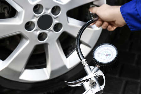 Mechanic checking tire air pressure at car service, closeup