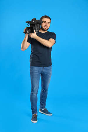 Operador con cámara de video profesional sobre fondo azul.
