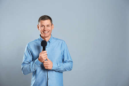 Male journalist with microphone on grey background. Space for text