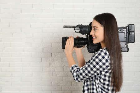 Operator with professional video camera near white brick wall