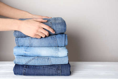 Woman folding stylish jeans on white wooden table, closeup. Space for text