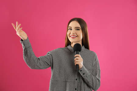Young female journalist with microphone on pink background Stock Photo