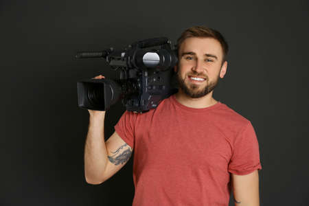 Operator with professional video camera on black background