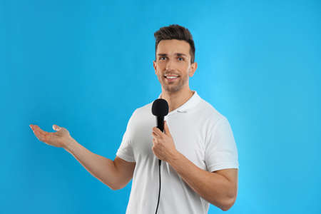 Young male journalist with microphone on blue background