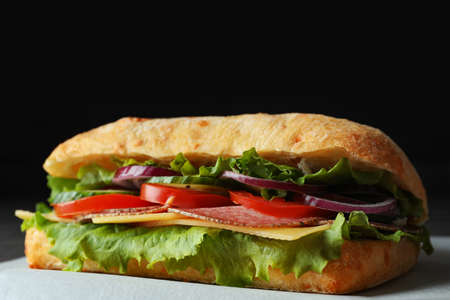 Delicious sandwich with fresh vegetables and salami on table