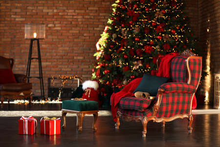 Santa Claus bag near armchair in room with Christmas tree Stock Photo