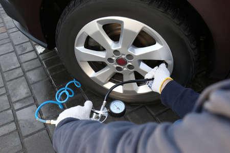 Mechaniker, der den Reifenluftdruck beim Autoservice überprüft, Nahaufnahme