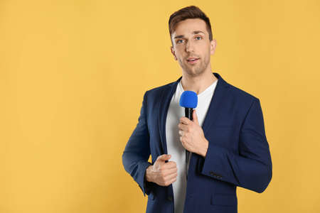 Young male journalist with microphone on yellow background. Space for text