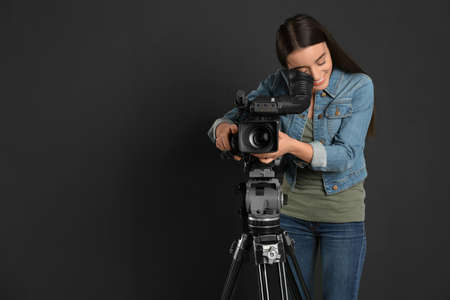 Operator with professional video camera on black background, space for text