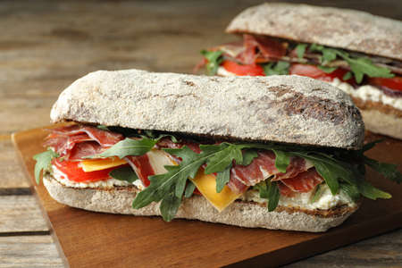 Delicious sandwich with fresh vegetables and prosciutto on wooden table, closeup