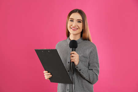 Young female journalist with microphone and clipboard on pink background Stock Photo