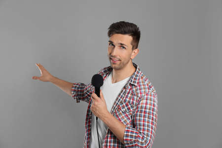 Giovane giornalista maschio con microfono su sfondo grigio Archivio Fotografico