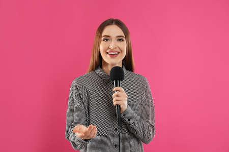 Giovane giornalista femminile con microfono su sfondo rosa