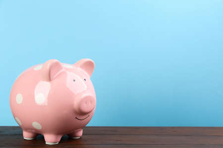 Pink piggy bank on wooden table against light blue background. Space for text