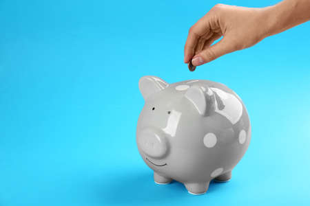 Woman putting coin into piggy bank on blue background, closeup Banque d'images