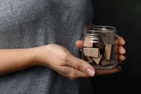 Woman holding glass jar with paper pieces, closeup on hands 스톡 콘텐츠