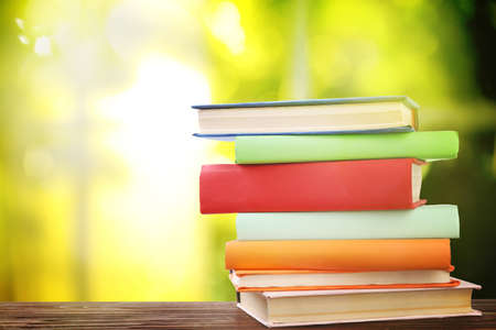 Stack of colorful books on wooden table against blurred green background. Space for text