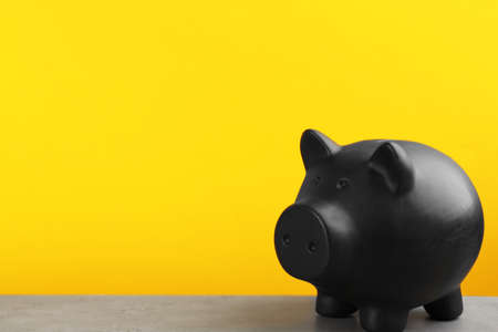 Black piggy bank on light grey table against yellow background. Space for text
