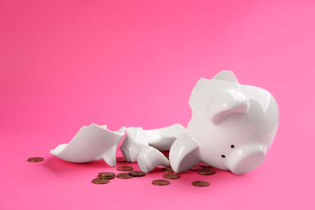 Broken piggy bank with coins on pink background