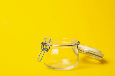 Open empty glass jar on yellow background 스톡 콘텐츠