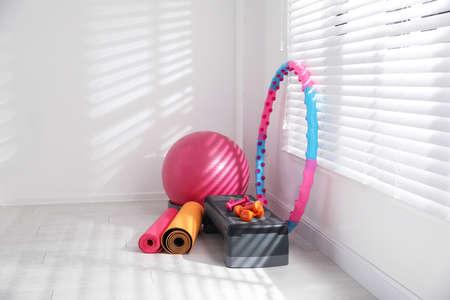 Different sports equipment near window in gym Reklamní fotografie