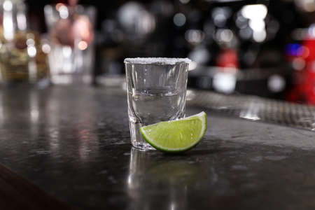Mexican Tequila shot with lime slice on bar counter