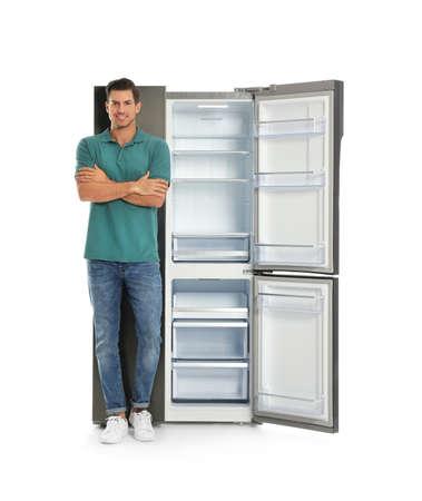 Man near open empty refrigerator on white background