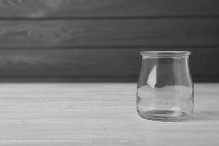 Empty glass jar on white wooden table, space for text