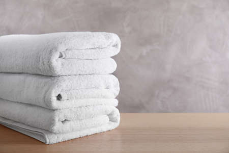 Stos czystych ręczników kąpielowych na drewnianym stole. Miejsce na tekst