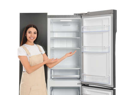 Young woman near empty refrigerator on white background Banque d'images