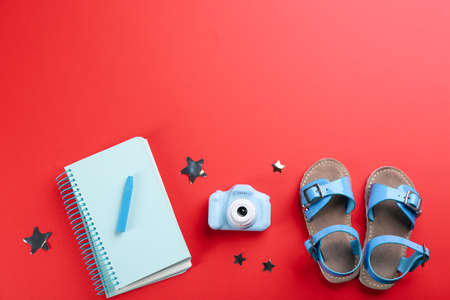 Flat lay composition with little photographer's toy camera on red background. Space for text