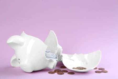 Broken piggy bank with money on violet background