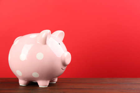 Pink piggy bank on wooden table against red background. Space for text