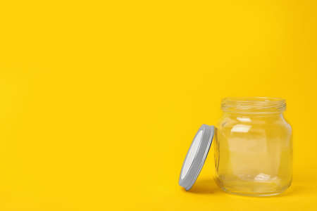 Open empty glass jar on yellow background, space for text