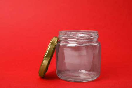 Open empty glass jar on red background Stock Photo