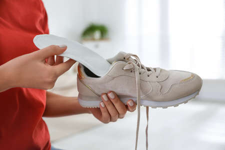 Woman putting orthopedic insole into shoe at home, closeup