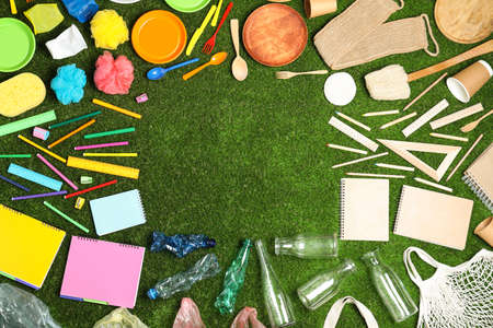 Flat lay composition with household goods on green grass, space for text. Recycling concept