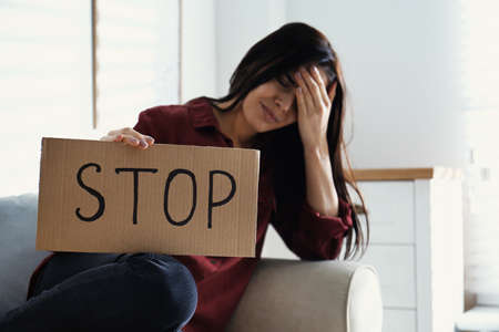 Crying young woman with sign STOP indoors. Domestic violence concept 写真素材