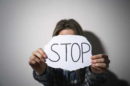 Abused young woman with sign STOP near white wall. Domestic violence concept