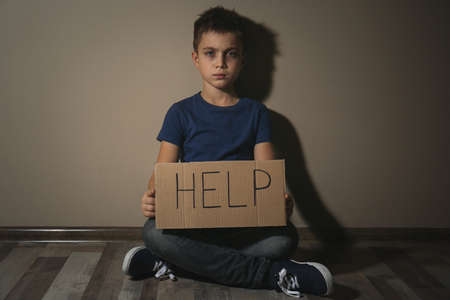 Abused little boy with sign HELP near beige wall. Domestic violence concept