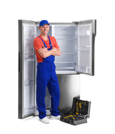 Male technician with tool box near refrigerator on white background