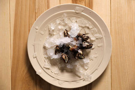 Fresh goose barnacle with ice on wooden table, top view