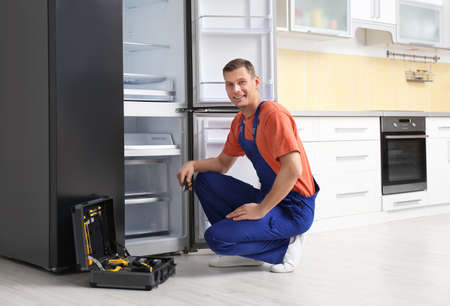 Male technician with pliers repairing refrigerator in kitchen
