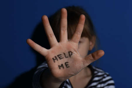 Abused little girl showing with phrase HELP ME near blue wall, focus on hand. Domestic violence concept