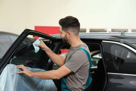 Worker washing tinted car window in workshop