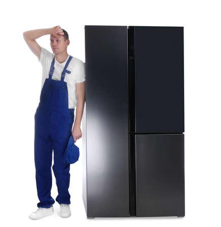 Professional worker near refrigerator on white background