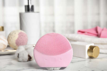 Modern face cleansing brush on marble table. Cosmetic accessory