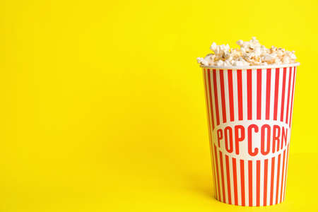 Tasty pop corn on yellow background, space for text